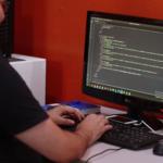 criação_de_sites_portais_agencia_mied_profissional na frente do computador digitando programação